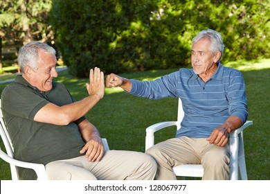 Two befriended senior men greeting each other with a youthful gesture