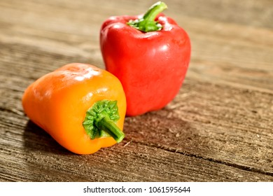 Two bell peppers, one yellow and one red on a wooden surface.