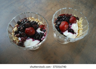 Two berries (strawberries, blueberries, blackberries) desserts with yogurt and rice flakes in glass cup. Fresh dessert.