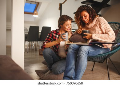 Two best female friends looking at family album.They sitting in living room and drinks coffee.