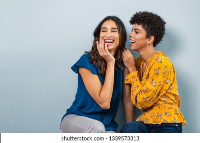 Two best friend girls whispering a secret. Beautiful woman and brazilian girl laughing and sharing gossip while sitting against wall with copy space. Stylish friends talking to each other and smiling.