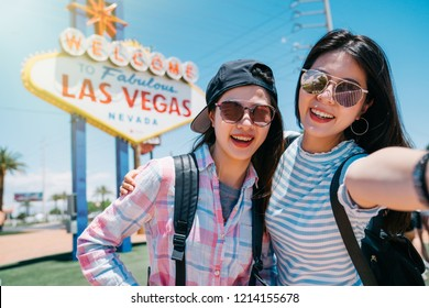 two best friend taking selfie with the welcome to fabulous Las Vegas sign in America. Friendship concept with young people having fun together taking self portrait photo in las vegas vacation.