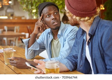 Two best friends or college mates having beer and using electronic gadgets at pub: Afro American man talking to his unrecognizable Caucasian friend, looking at him in shock and full disbelief