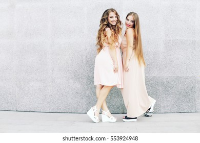 Two best friends embracing over gray wall. Young women having great time together. Sisters at the prom with gorgeous long curly hair. Professional make-up and hairstyle.