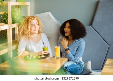Two best friends enjoying nice conversation during lunch in modern cafe interior. African woman dining at restaurant together with white curly female. People, leisure, communication and friendship.