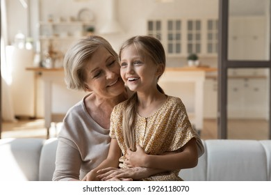 Two best friends. Excited little girl grandchild sit on loving mature grandmother knees share secrets dreams. Caring retired grandma older age female babysitter sit on sofa hold small kid on laps talk