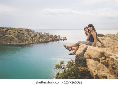 Two best friends female travelers on top of a cliff looking at the camera, in Malta