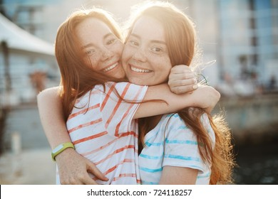 Two best friends and ginger twins hugging, rejoicing. Spending the best time of life together. Sisterhood and friendship concept.