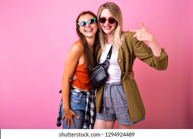 Two  best friends girls hugs and smiling, modern casual trendy hipster looks, pink background, students fun.