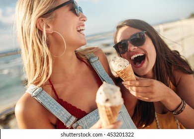 Two best friends having ice cream together outdoors. Close up of young women eating ice cream and laughing.