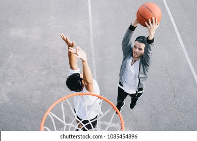 Two best friends are playing basketball near the basket. One of them is trying to defence his territory with the basket on there while another one is going to throw the ball into the basket