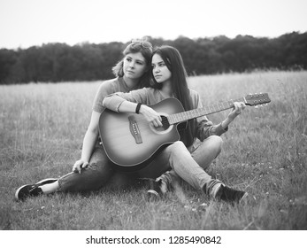 Two best friends sit on the grass and play the guitar. Black and white