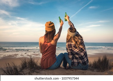 Two best friends sitting on the coastline toasting to friendship