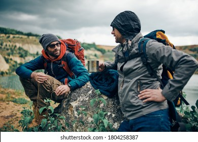 Two best friends sitting and standing in nature, taking a break and drinking warm drinks on camping trip.