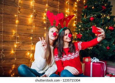 Two best friends taking selfie in bedroom near Christmas tree
