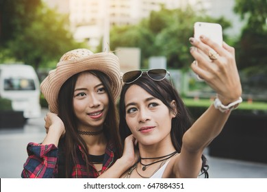 Two best friends taking a selfie with smart phone.