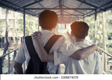 Two best male friends walking on bridge, with thinking and hugging.