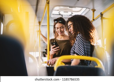 Two best young sweet girl friends standing in a bus and looking in a telephone.
