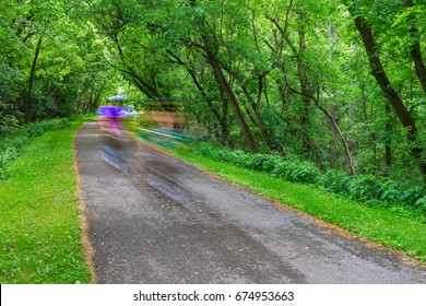 Two bicycle riders in motion blur on the Little Miami Scenic River Trail bike path, Southwestern Ohio, USA