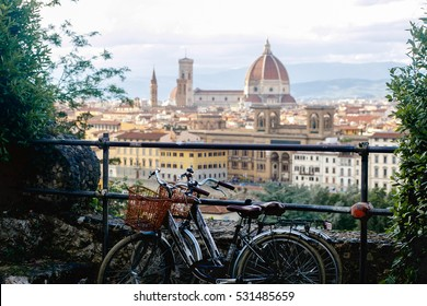 Two bicycles with baskets stand on the road with a great cityscape behind them