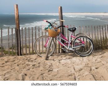 Two bicycles leaning against a dune fence at the beach at the New Jersey shore with ocean waves in the background