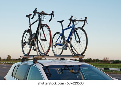 two bicycles mounted on roof of car