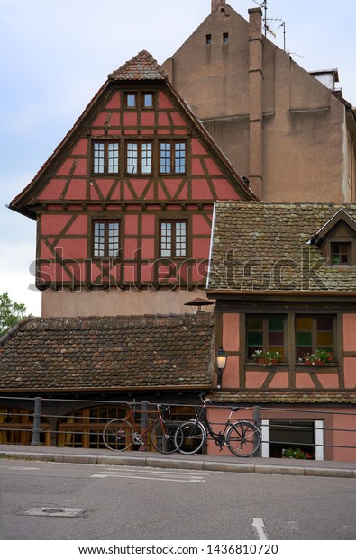 Two bicycles are parked close to traditional Architecture in Strasbourg, France.