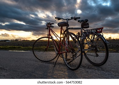 Two bicycles parked on a country road with dramatic sky during sunset