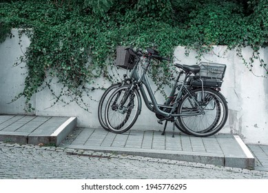 Two bicycles parked on the sidewalk near a concrete wall and green vegetation. Bicycles on the sidewalk in Sellin city, on Rugen island, in north Germany.