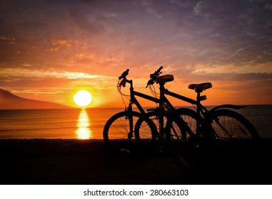Two bicycles standing on the beach at sunset.