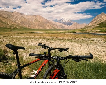 Two bicycles in a wide beautiful plain and Mount Damavand  in the background.
