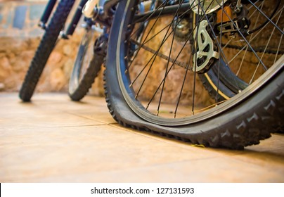 Two bicycles at the yard, one with a flat tyre