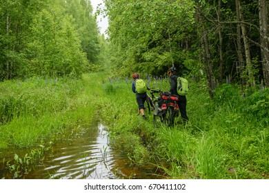 Two bicyclists crossing puddle, Vladimir Region, Russia