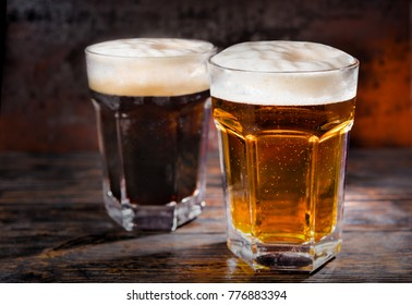 Two big glasses with freshly poured dark and light beer and head of foam on wooden desk. Food and beverages concept