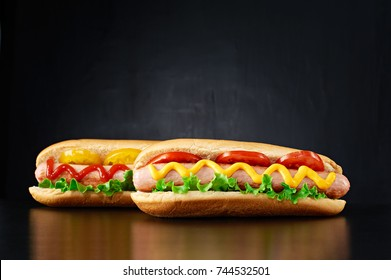 Two big hotdog with sausage tomatoes, mustard, ketchup and salad isolated on black background. Front view.