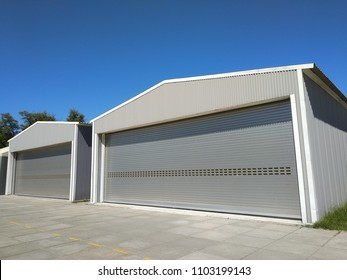 Two big  industrial metal hangar or warehouse with closed doors. Metal garage building for manufacturing usage. Place for storage of transport. Side view