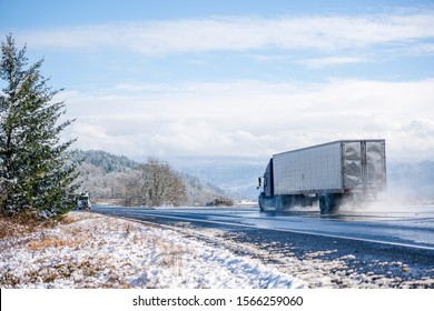Two big rigs semi trucks with different semi trailers go towards each other following each his own route on the winter dangerous wet road raising clouds of water dust from melting snow