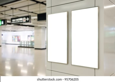Two big vertical / portrait orientation blank billboard on modern white wall with subway concourse background