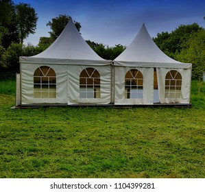 Two big white tents for events in the woods on a festival meadow