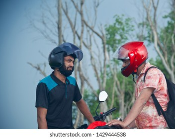 Two bike riders talking to each other standing in a place