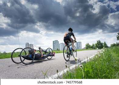 two biker by race cycling contest. one sporsmen is on the recumbent bicycle, other one is on the normal bike.