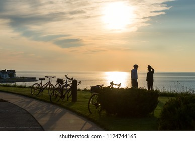 Two bikers taking break at the sunset time on Lake Michigan