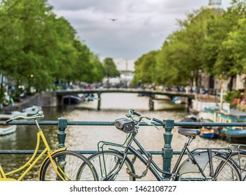 Two bikes chained to the rails of a bridge over a canal in Amsterdam, The Netherlands (Holland), Europe