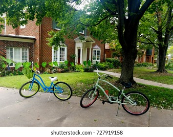 Two Bikes Parked In Front Of A Brick House In The Summer