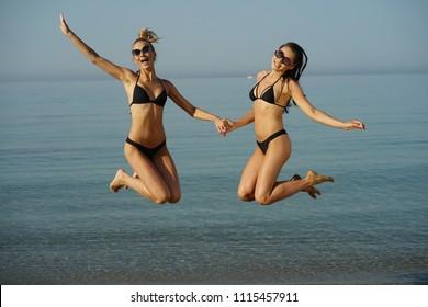 Two bikini clad women jumping on the beach