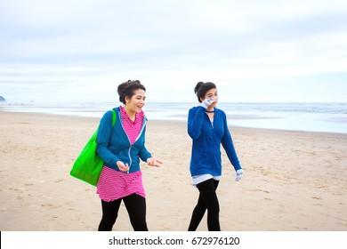 Two biracial Asian Caucasian  teenage girls talking while walking along beach on cool cloudy day