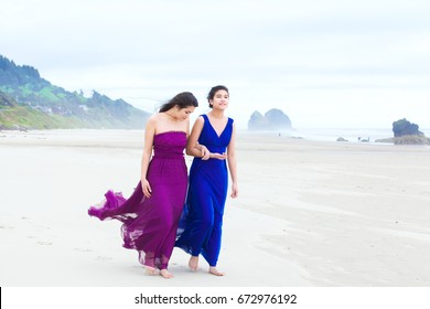 Two biracial Asian Caucasian  teenage girls in formal dresses  talking while walking along beach on cool cloudy day