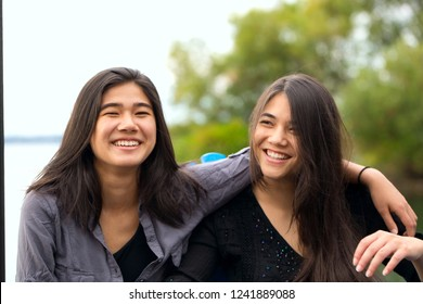Two biracial sisters, Asian Caucasian teen girls, outdoors smiling by lake with arms over the shoulders