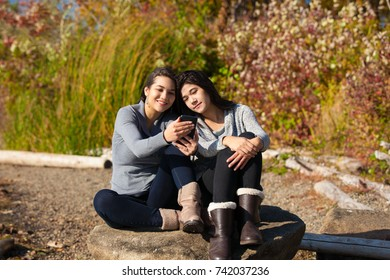 Two biracial teen girls sitting on rock on sunny day in autumn looking at smart phone screen by lake