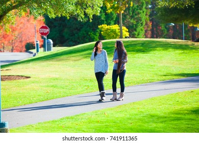 Two biracial teen girls or  young women talking while walking through park together in autumn season